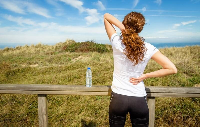 athletic-woman-touching-neck-and-back-muscles-by-injury