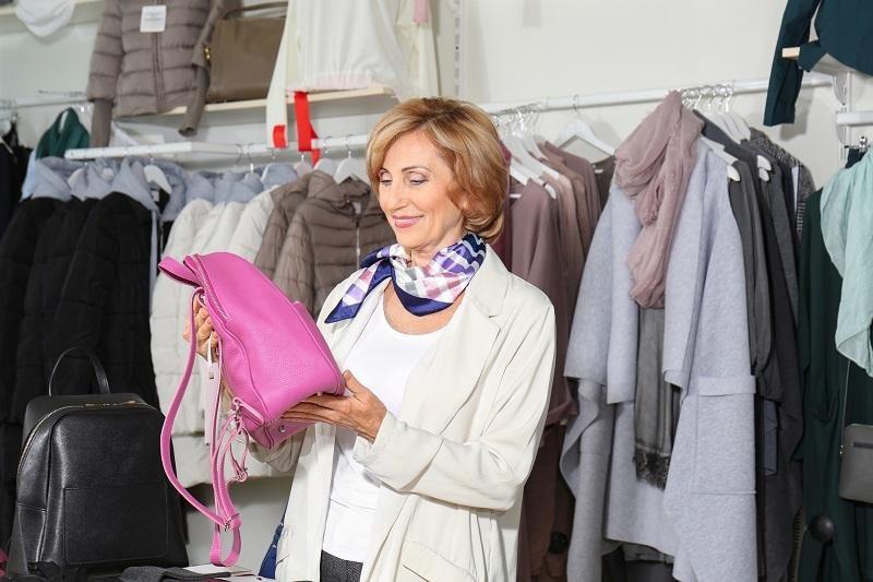 elderly-woman-choosing-bag-in-store