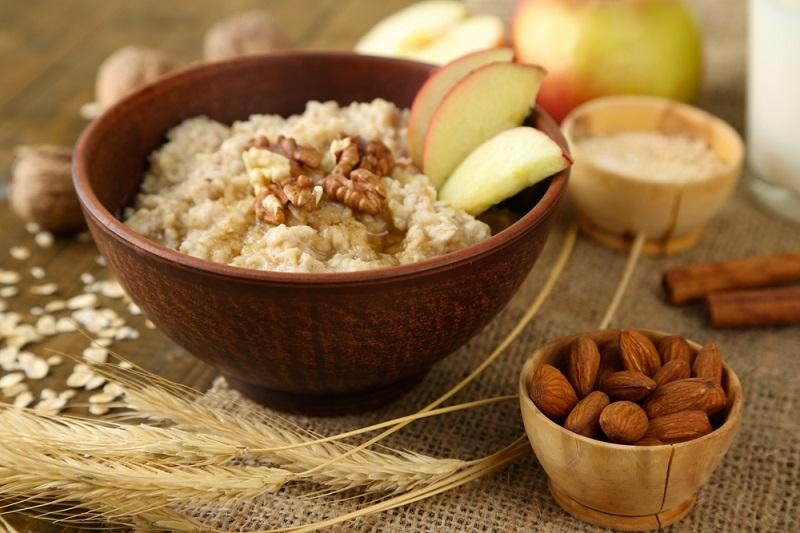 tasty-oatmeal-with-nuts-and-apples-on-wooden-table