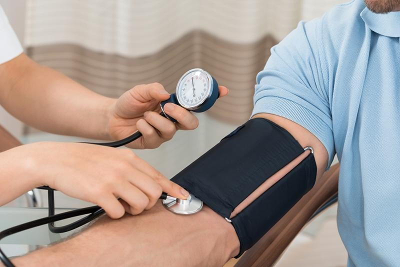 doctor-measuring-blood-pressure-of-male-patient