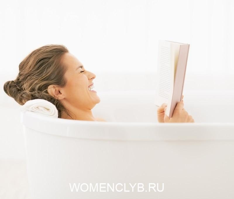 smiling-young-woman-in-bathtub-reading-book
