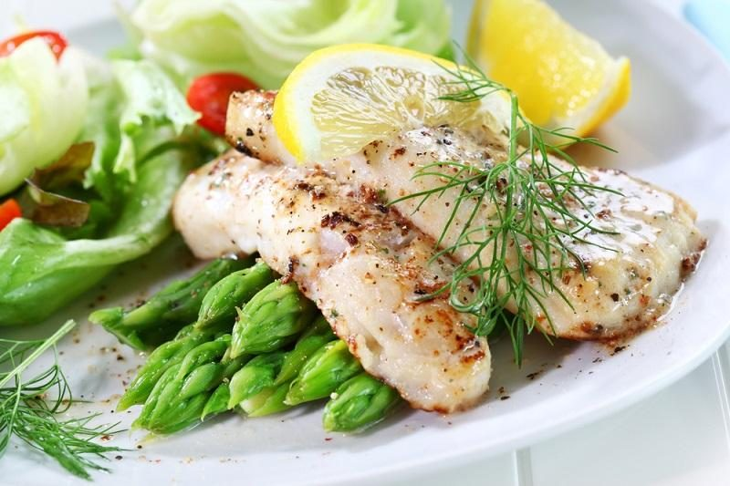 fried-fish-on-green-asparagus-with-salad