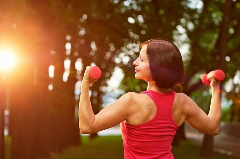 aged-woman-working-out-with-small-dumbbells-in-the-park-in-the-m