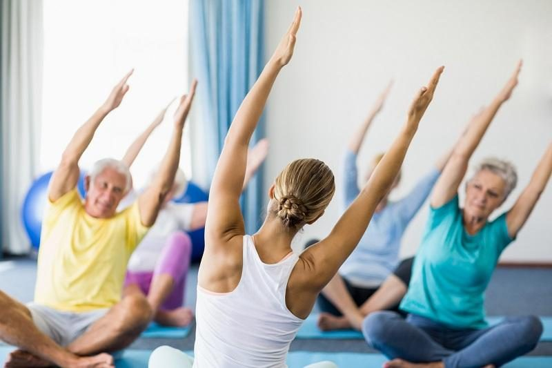 instructor-performing-yoga-with-seniors