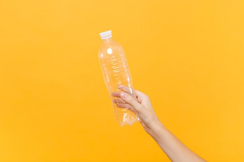 close-up-female-hold-in-hand-transparent-clear-empty-blank-plastic-bottle-for-soda-water-isolated-on-yellow-background-packaging-template-mockup-thirst-service-concept-copy-space-advertising-area