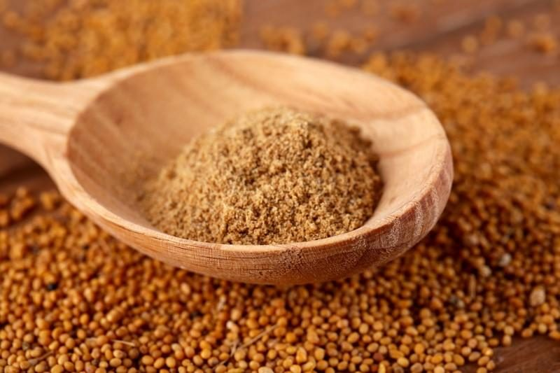 mustard-powder-in-wooden-spoon-on-mustard-seeds-on-wooden-background